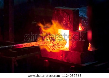 Burning  in a blacksmith forge.  Making metal items in smithy. In the smithy a red-hot iron piece in a hot fire flame is ready for further processing Stock fotó ©