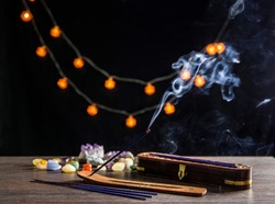 Burning incense stick and its smoke, wooden base and wooden storage box for sticks on dark black background with semi precious stones crystals. Spirituality concept.