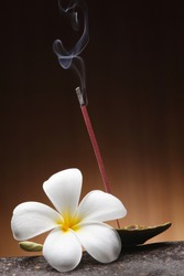 Burning incense stick and tray, studio shot