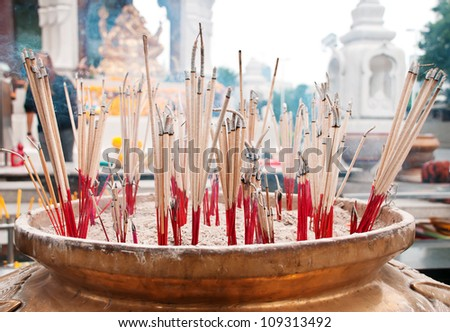 burning incense sticks in brass Incense bowl at buddhist shrine