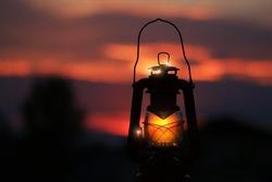Burning lantern illuminated by and orange sunset