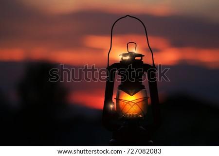 Burning lantern illuminated by and orange sunset Foto d'archivio ©