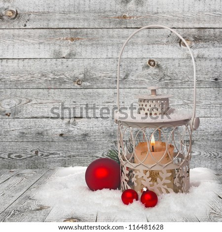 Burning lantern in the snow on wooden background
