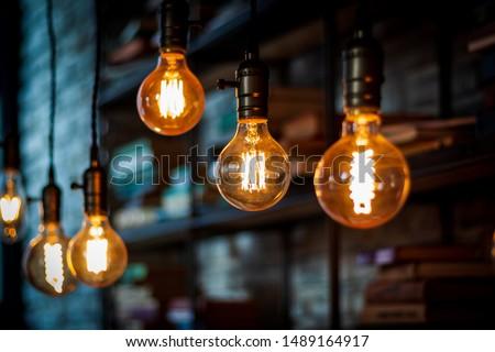 Burning light bulbs near bookshelf #1489164917
