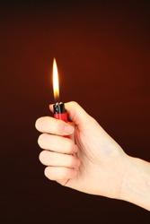 Burning lighter in female hand, on dark brown background