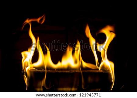 Burning log with black background.