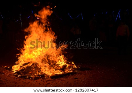 Burning Lohri / Holi bonfire to celebrate, Punjabi festival of harvest in north India. Celebrated by newly weds in winter season with pop corn, sesame chikki and peanuts groundnuts as prasad offering
