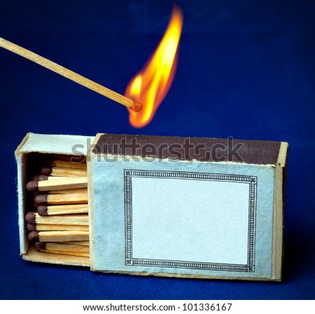Burning match and boxes of matches