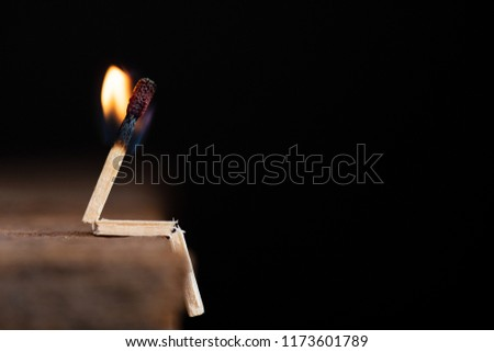 Burning match human sitting on wooden table on a dark background.