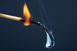 Burning match on a dark background