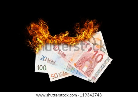 Burning money, euro bills on fire, isolated on black