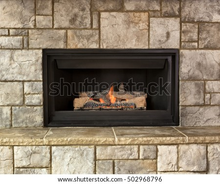 Burning natural gas fireplace surround by stone #502968796