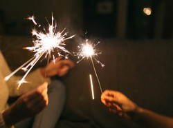 Burning New Year sparkler. Bengal light scattering into small sparkles. Celebrating christmas and new year 2021