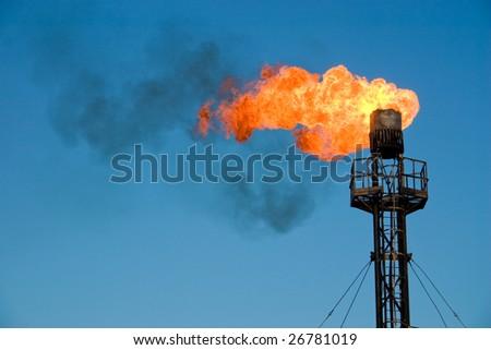Burning oil flare on a blue sky