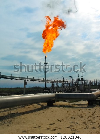 Burning oil gas flare over the blue sky