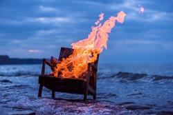 Burning old armchair on the seashore