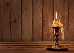 burning old candle vintage bronze candlestick on wooden background.