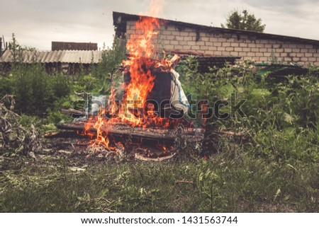 Burning old dry grass in the garden. Destruction of green space. Danger to the ozone layer. Environmental disaster. Ecology, destruction #1431563744