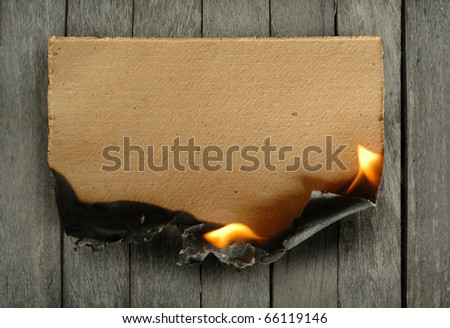burning paper on wood background