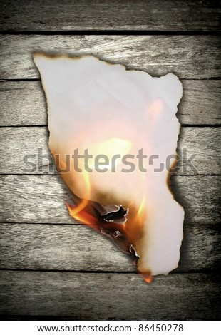 Burning paper on wooden wall