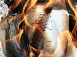 Burning paper with typed russian letters