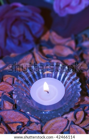 burning purple candle on a decorative background, still life scene
