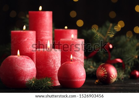 Burning red candles with Christmas decor on table against blurred lights #1526903456