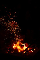 Burning red hot sparks fly from large fire in the night sky. Beautiful abstract background on the theme of fire, light and life.  Fiery orange glowing flying away particles over black background.