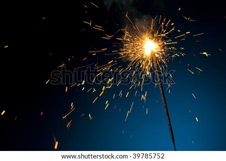 burning sparkler on blue