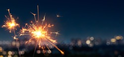Burning sparkler with blurred bokeh cities light background