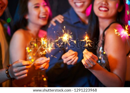 Burning sparklers in hand of happy partying Vietnamese people #1291223968