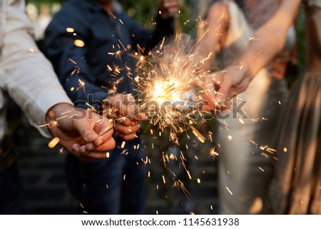 Burning sparklers in hands of party guests #1145631938