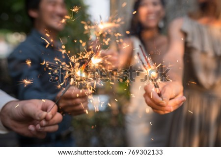 Burning sparklers in hands of party guests #769302133