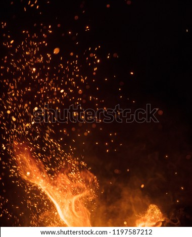 Burning sparks flying. Beautiful flames. Fiery orange glowing flying away particles on black background. #1197587212