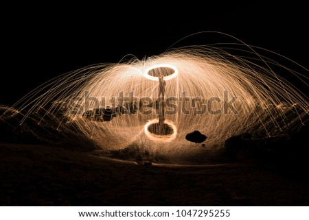 Stock Photo Burning steel wool spinned near the sea. Showers of glowing sparks from spinning steel wool