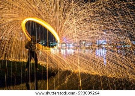 Stock Photo Burning Steel Wool spinning by unrecognized man at Putrajaya Malaysia. Showers of glowing sparks from spinning steel wool. Subject soft focus and blurred.