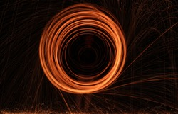 Burning Steel Wool spinning. Showers of glowing sparks from spinning steel wool. Visible noise due to low light condition.
