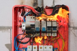 Burning switchboard from overload or short circuit on wall close-up. Circuit breakers on fire from overheating due to poor connection or poor quality wires. Faulty home wiring concept