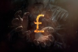 Burning symbol of british pound with man in the background. Conception of risk management in money trading at currency market