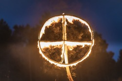 Burning symbol of the sun, a sun cross or solar wheel at pagan reenactment of Kupala Night, called in Poland Noc Kupaly. Slavic holiday celebrated on the shortest night of the year, summer solstice