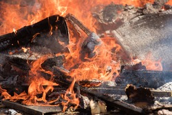 Burning trash with visible red flames and charred wood.