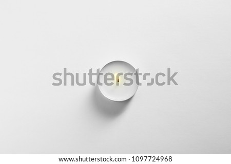 Burning wax candle on white background, top view #1097724968