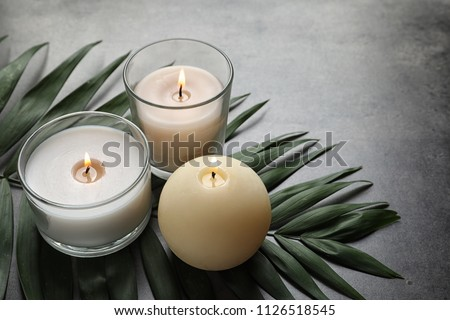Burning wax candles and tropic leaf on table #1126518545