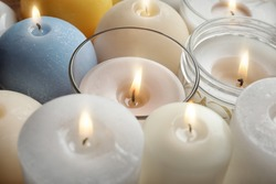 Burning wax candles of different shapes and colors, closeup
