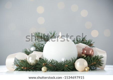 Burning white candle with Christmas decor on table against blurred lights #1534697915