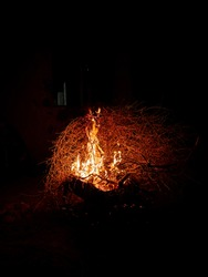 Burning wood at night. Campfire at touristic camp at nature. Flame fire sparks on dark abstract background. Cooking barbecue outdoor. Hellish fire element. Fuel, power and energy
