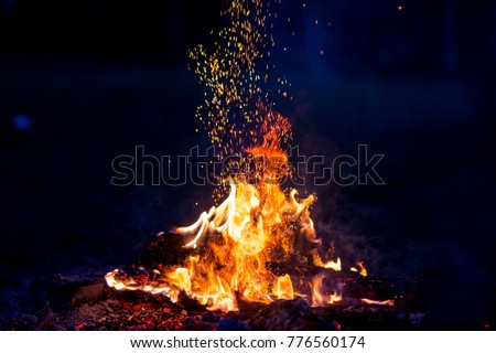 Burning wood at night. Campfire at touristic camp at nature in mountains. Flame amd fire sparks on dark abstract background. Cooking barbecue outdoor. Hellish fire element. Fuel, power and energy