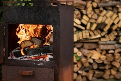 Burning wood fire in a rusty old metal wood stove standing outside with a heap pile of wooden logs stacked in the background ready to be used to create warmth in the outdoor garden. Simple life