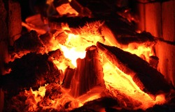 Burning wood, hot coals and fire in the fireplace
