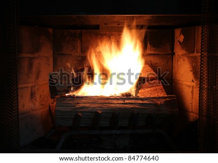 Burning wood in a brick fire place.